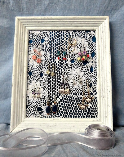 Earring organizer made with a frame, a blue satin blouse and a doily.