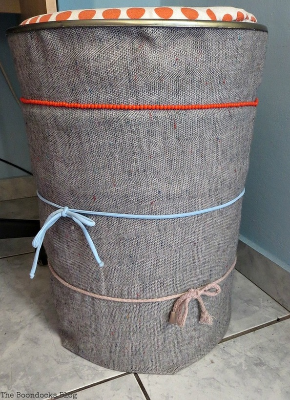 A stool covered with a pillow like fabric upcycle, Tweety's Storage Stool www.theboondocksblog.com