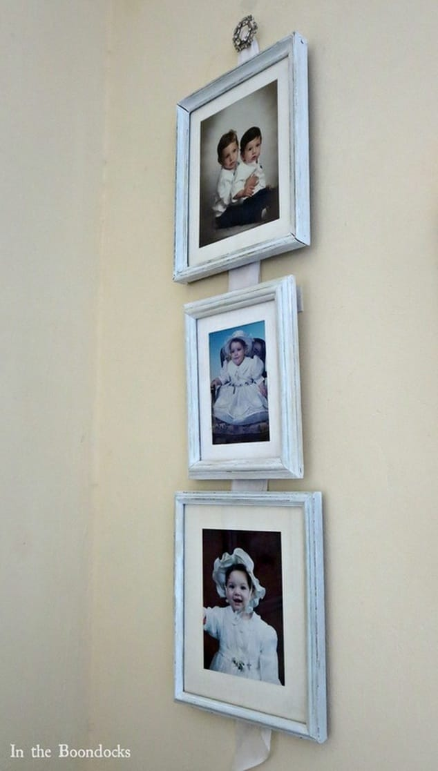 three picture framesthat have been painted to eliminate the metallic colors,  hanging on white fabric strip, Banishing the Shine www.theboondocksblog.com