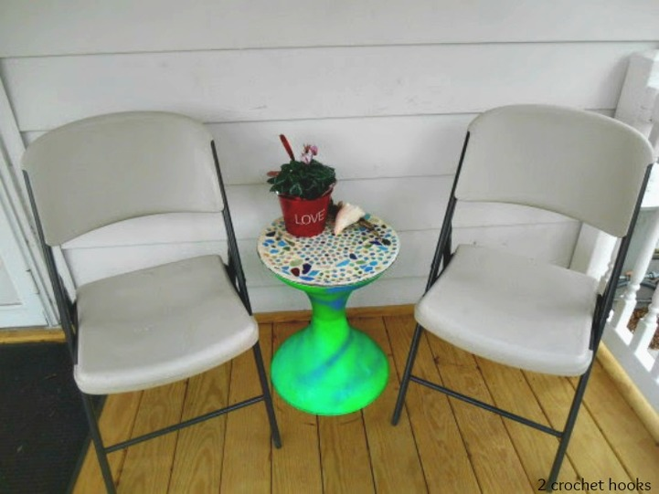 Finished sea glass mosaic table top next to two folding chairs.