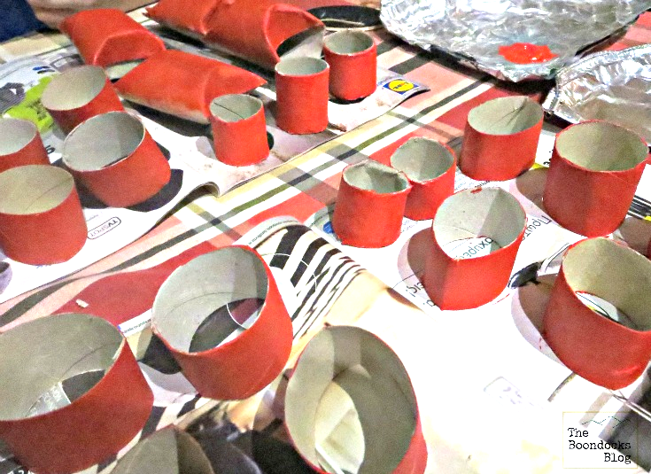 Painting toilet paper rolls with red paint to make this heart craft.