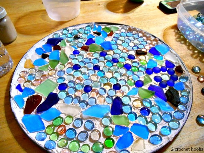 Pizza pan covered with grout and decorated with sea glass and marbles.