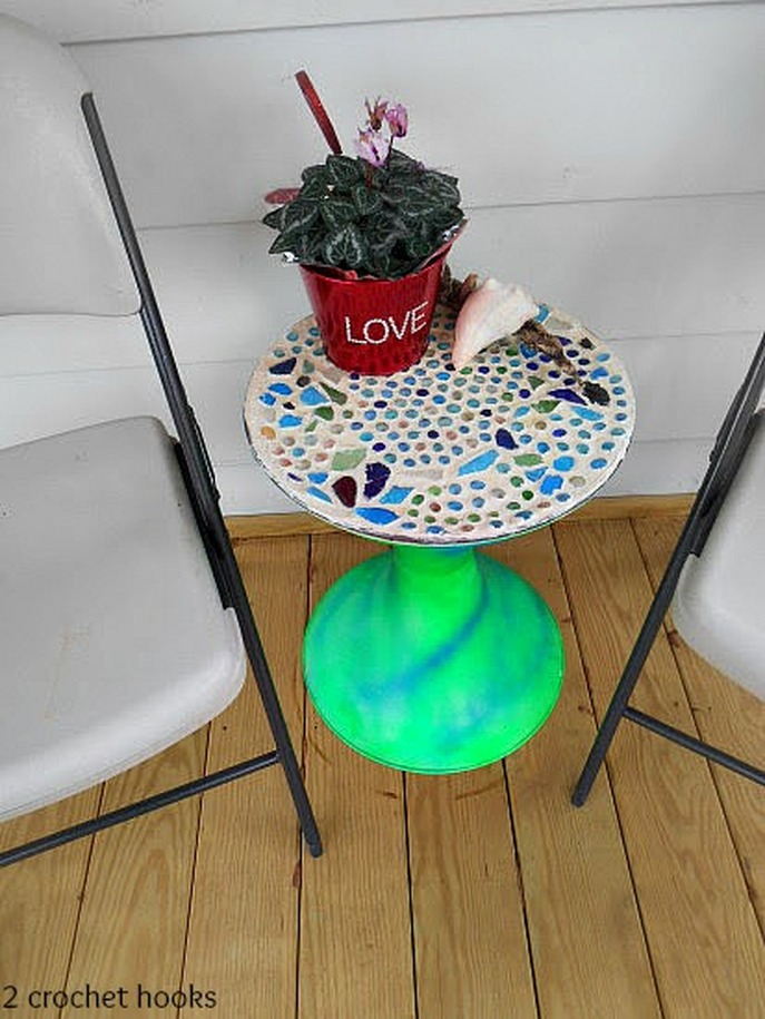 Sea glass mosaic table beside two folding chairs.