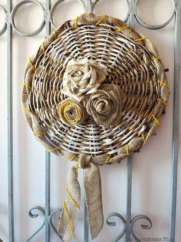 using the bottom of a basket to make a wall decor with burlap yarn and ribbons, #Easywallart #CraftyArt #Repurposedbasket #RusticwallArt The Crafty Bottom www.theboondocksblog.com