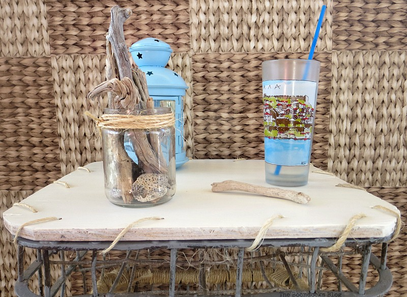 Close up of the white top of the table with a drinking cup, lantern and driftwood in a jar placed on top.