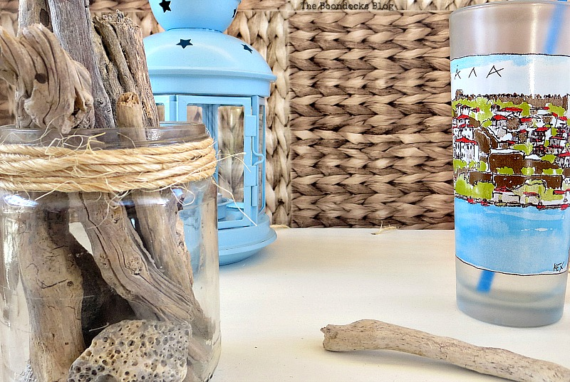 Close up of table top items, including a blue lantern, a drinking cup and driftwood in a jar.