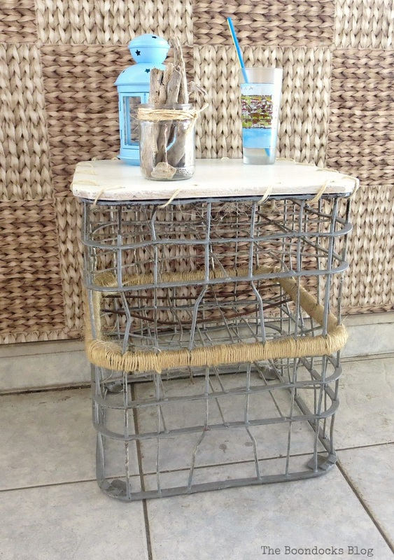 The finished wire milk crate table with a drinking cup, lantern and driftwood in a jar placed on top.
