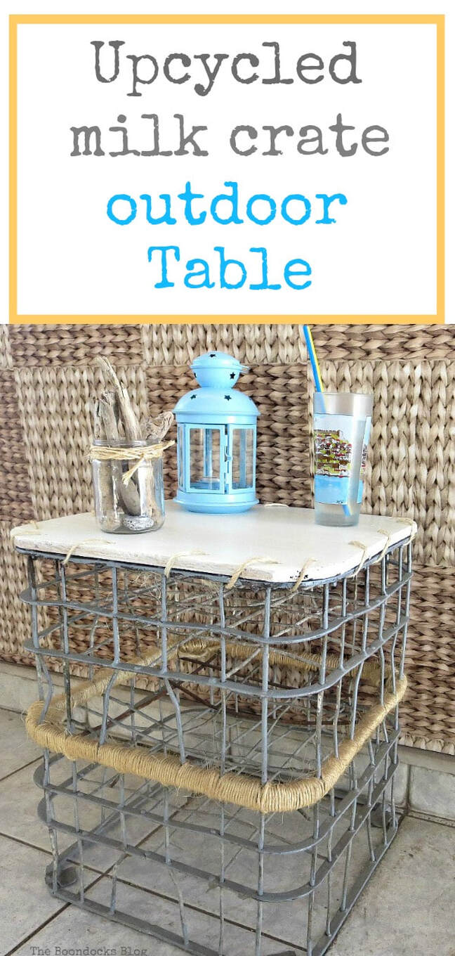 The finished wire milk crate table with a drinking cup, lantern and driftwood in a jar placed on top. Overlay says upcycled milk crate outdoor table.""
