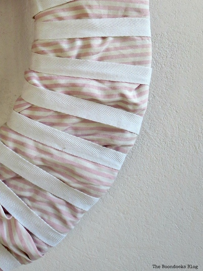 adding white ribbon to the striped fabric, The lopsided Summer Wreath www.theboondocksblog.com
