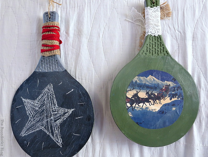 2 rackets, one with paint and Christmas scene the other with blackboard paint, Christmas in July - Repurposed Barbie Paddles www.theboondocksblog.com