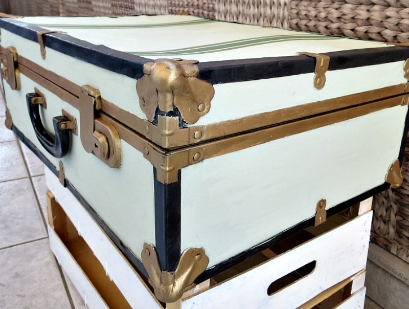 Corner view of the painted vintage suitcase.
