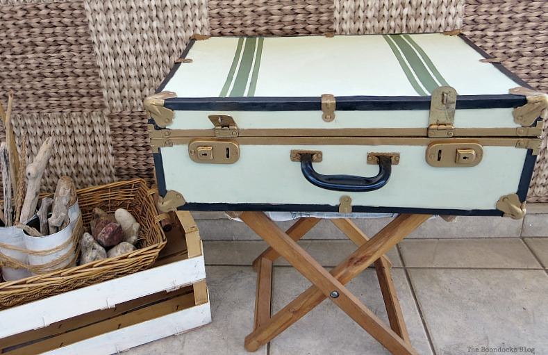 The finished vintage suitcase after it's been painted white, gold, green and black. It's placed on top of a brown table and beside a basket filled with driftwood and rocks.