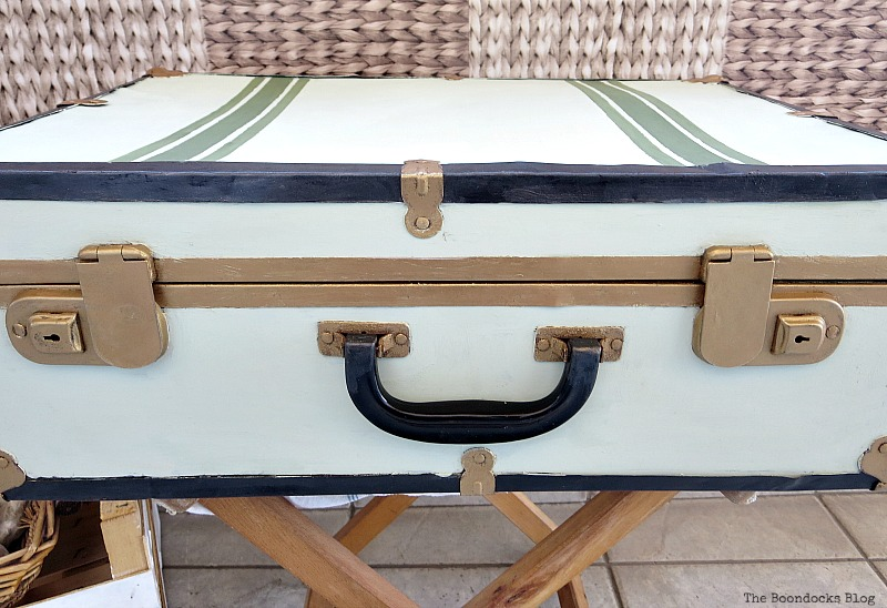 Showing how the front of the suitcase has gold clasps that are not symmetrical to the handle.