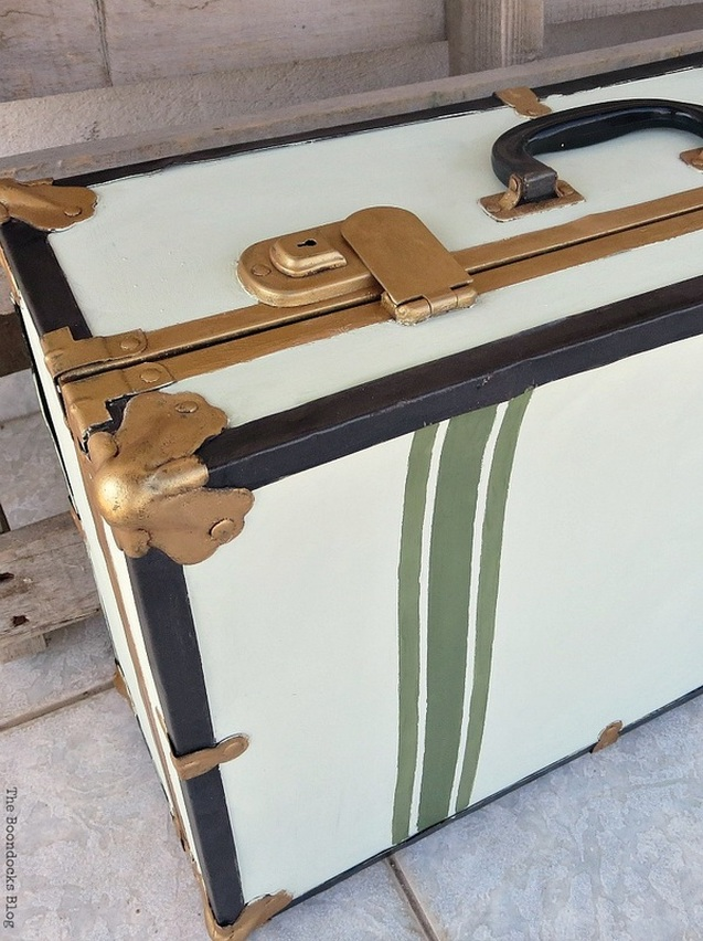 Close up of green painted stripes, gold clasps and gold bumper on the vintage suitcase.