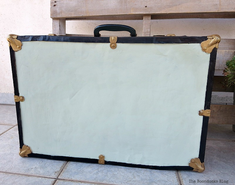 The bottom of the vintage suitcase, ust painted with white paint.