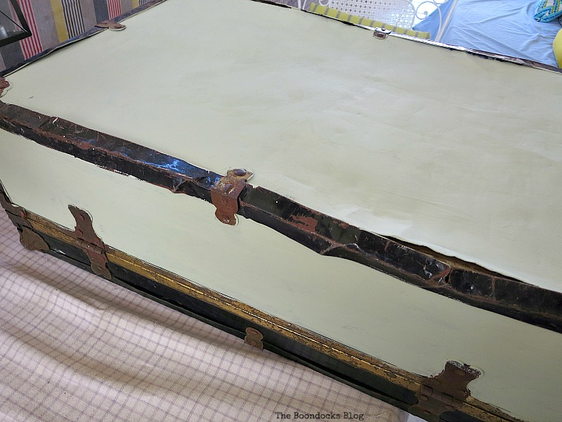 Painting the sides top and bottom of a vintage suitcase white.