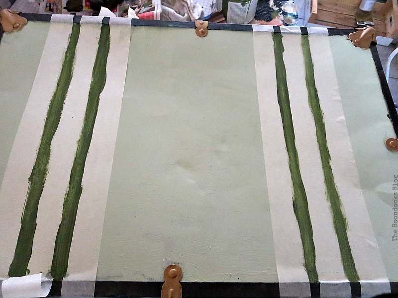 Painting green stripes on top of suitcase to look like straps.