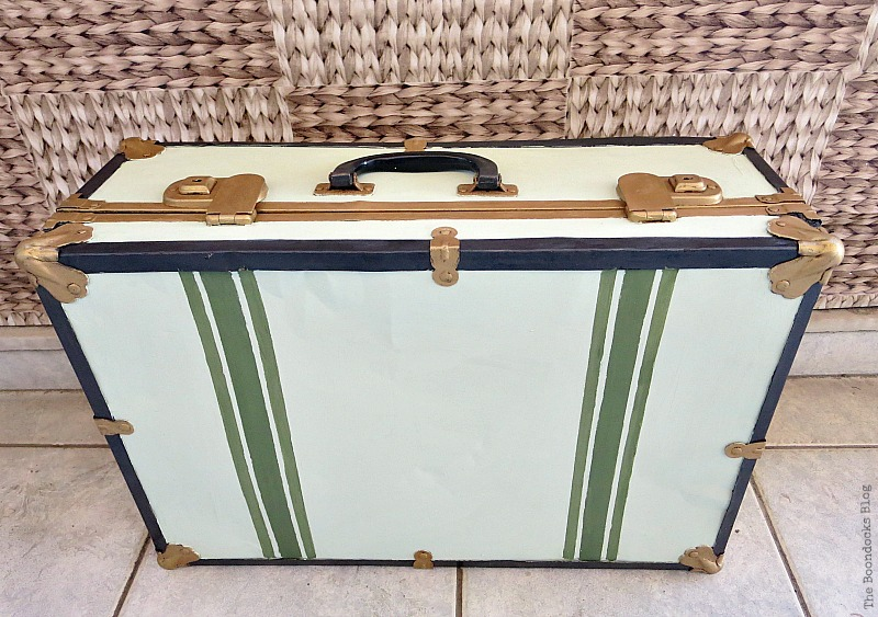 The finished vintage suitcase after it's been painted white, gold, green and black.