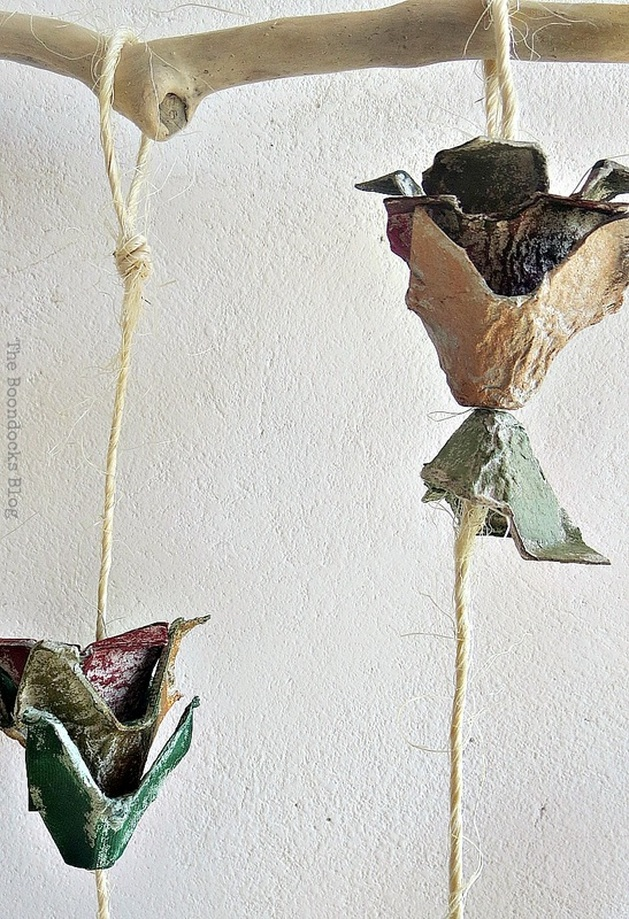 Egg carton flowers hanging from a piece of driftwood.