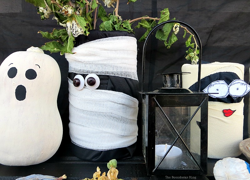 A larger mummy wrapped in black fabric and gauze with button eyes, Fun and Easy Halloween Vignette - Int'l Bloggers Club Challenge www.theboondocksblog.com