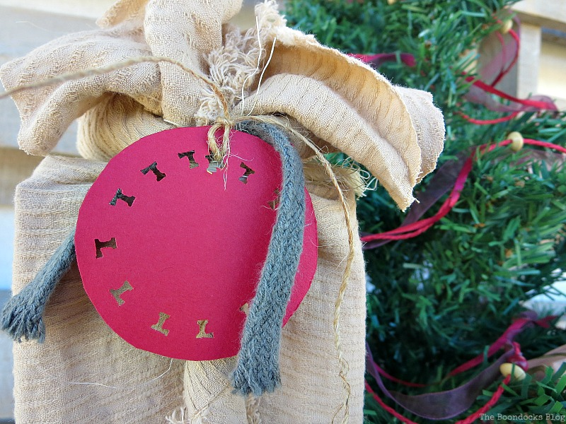 Tag made with hole punch in L shape, How to Repurpose vintage fabric for gift wrapping, the boondocksblog.com