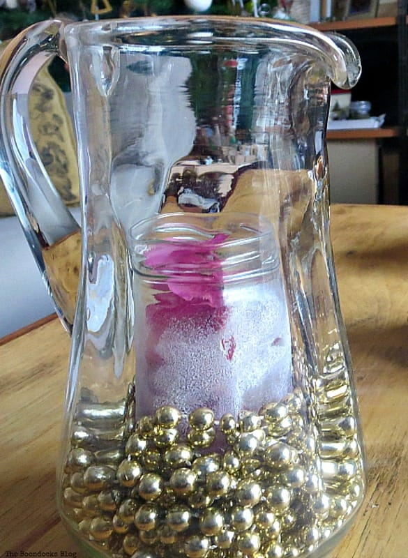 A glass jar inside a pitcher with gold garland, A Repurposed Spice Rack vignette for Christmas, www.theboondocksblog.com