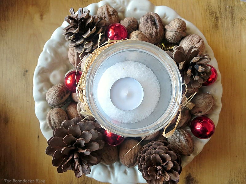Tealight inside a jar atop of a plate with globes pinecones and walnuts,A Repurposed Spice Rack vignette for Christmas, www.theboondocksblog.com