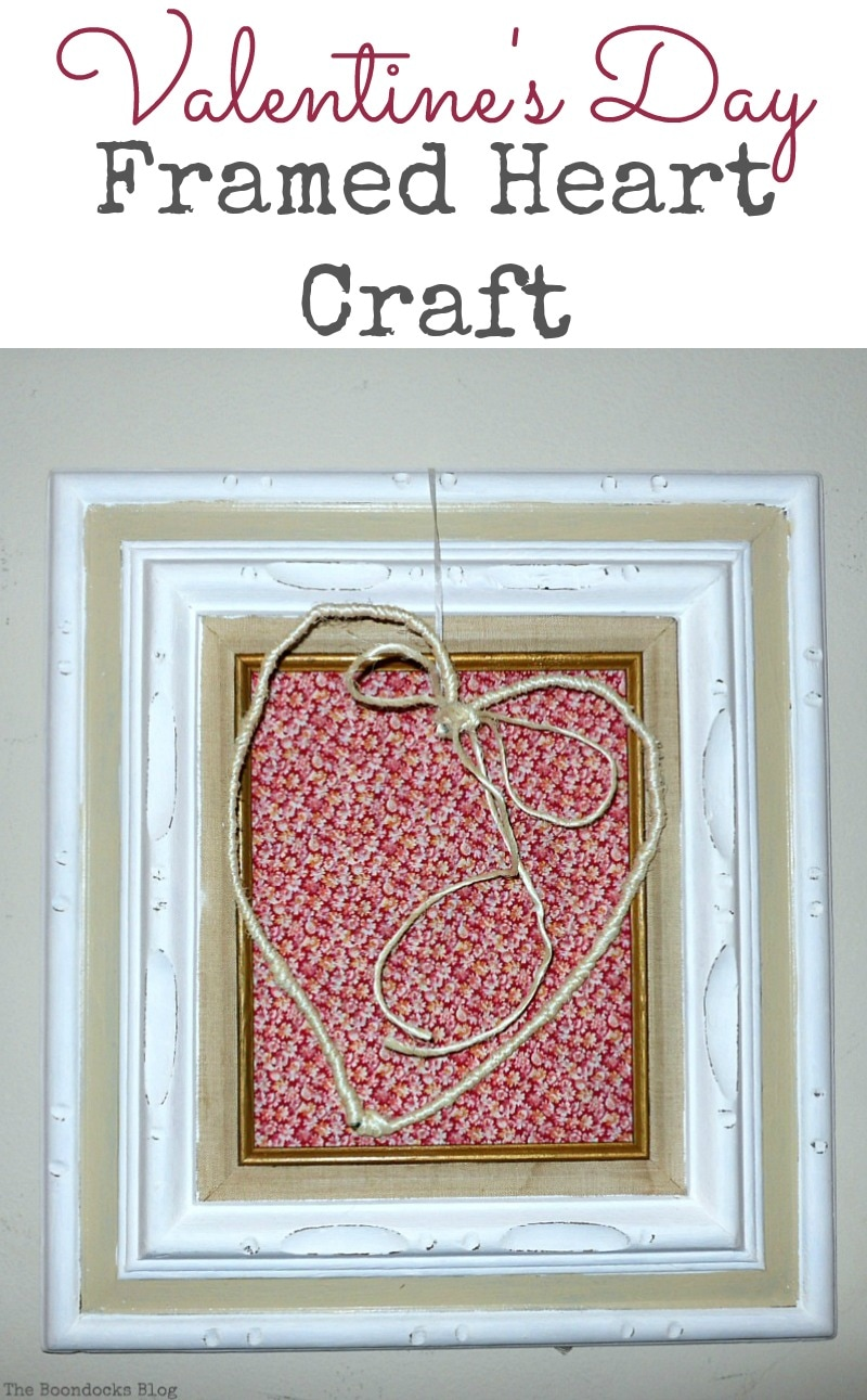 Wire heart wrapped in twine and hung over a frame that is covered with a red fabric, Valentine's Day Framed Heart Craft - Int'l Bloggers Club www.theboondocksblog.com
