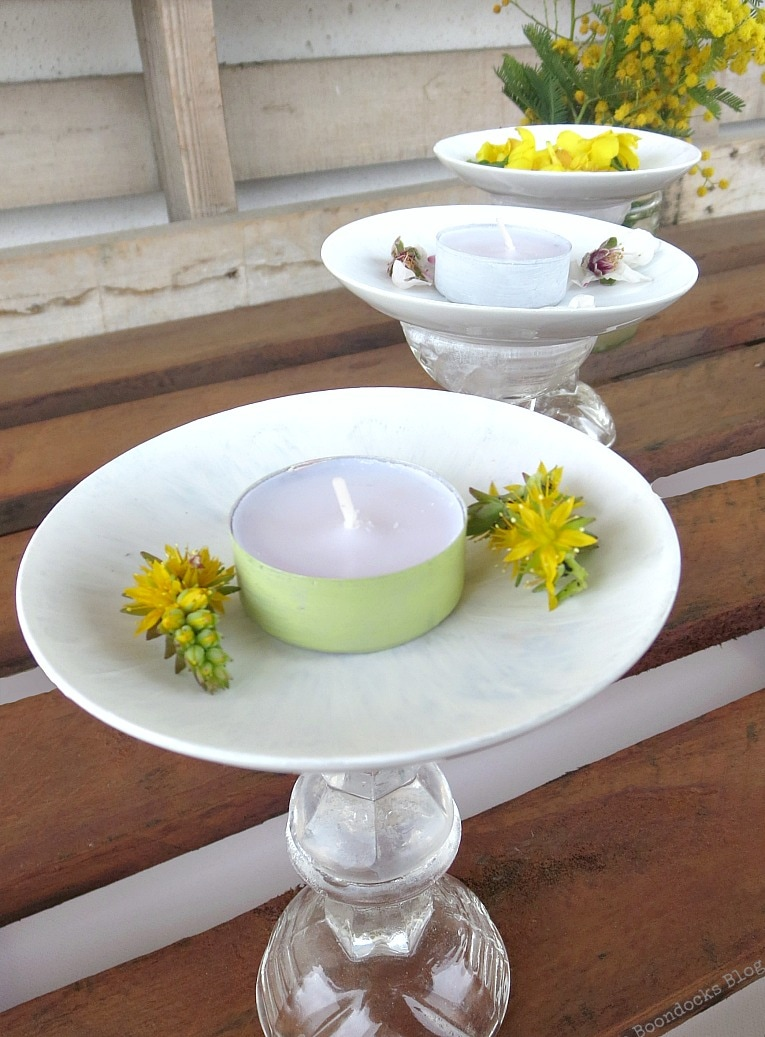 tops of saucers with flowers and tealights, Repurposed Cordial Glasses and Saucers for a Spring Craft Pedestal, www.theboondocksblog.com