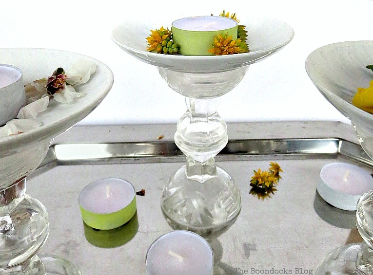 Pedestals placed on a silver tray with tea lights and flowers.