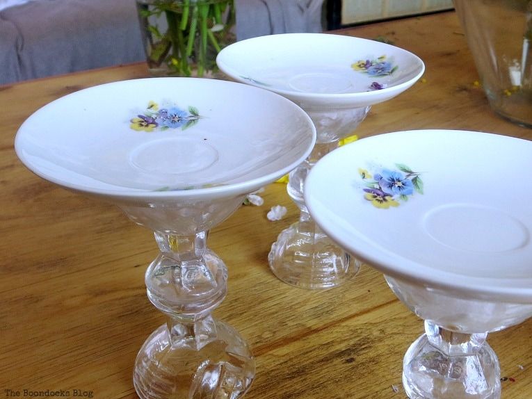 gluing saucers on top of the glass pedestals, Repurposed Cordial Glasses and Saucers for a Spring Craft Pedestal, www.theboondocksblog.com