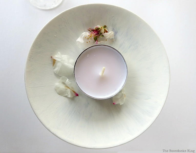 Almond flowers and a tealight sitting on the painted saucer.