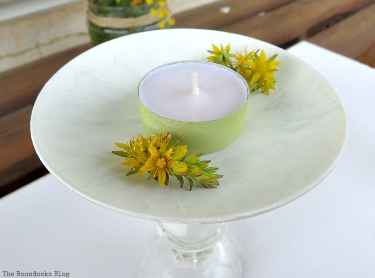 Painted tealight with yellow succulent flowers sitting on the painted saucer.