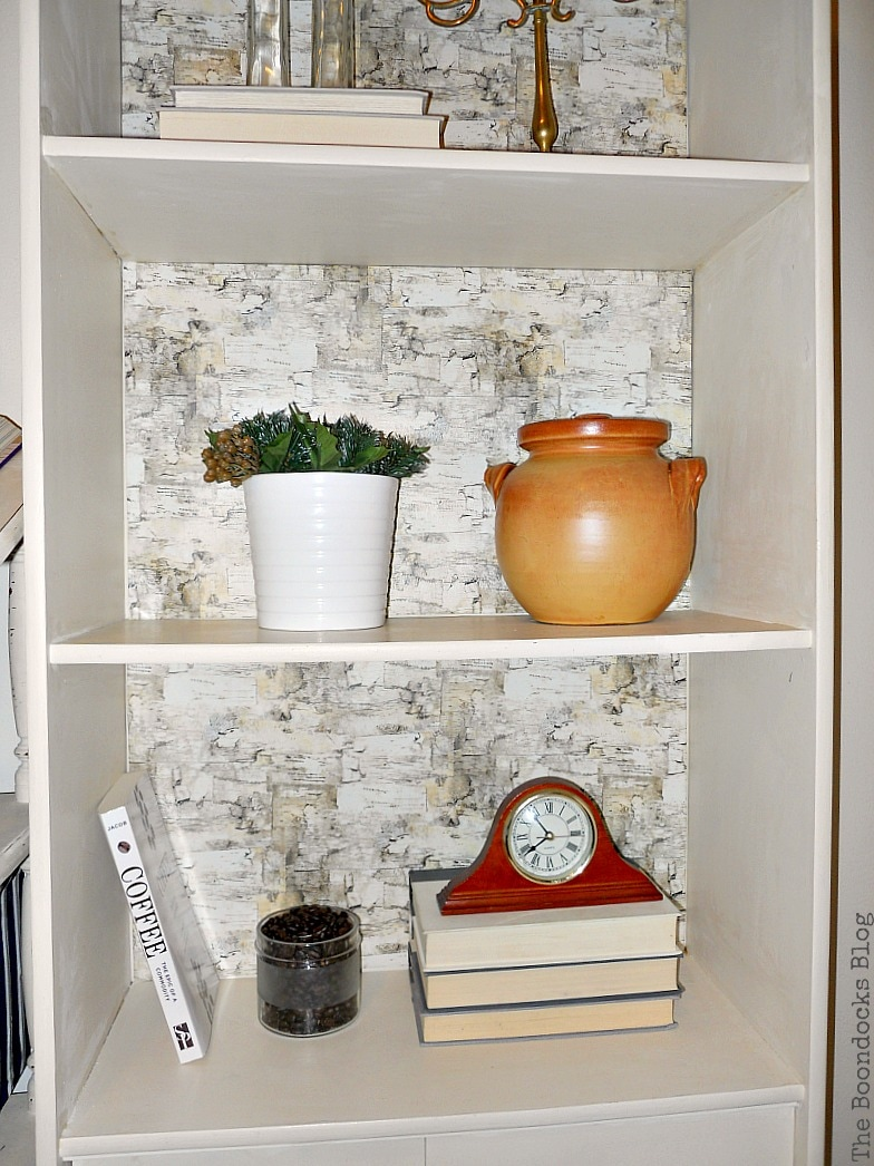 Close up of shelf decorated with clay pot, a plant, books and a clock.