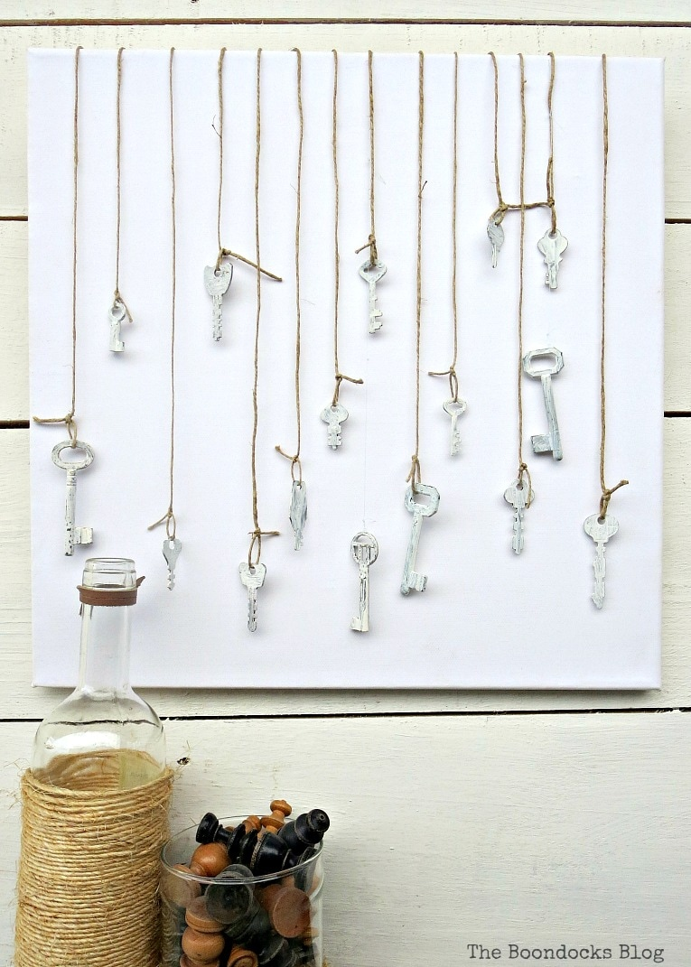 Canvas with chalky painted keys hanging from twine, How to Make Simple Canvas Wall Art with Keys, www.theboondocksblog.com
