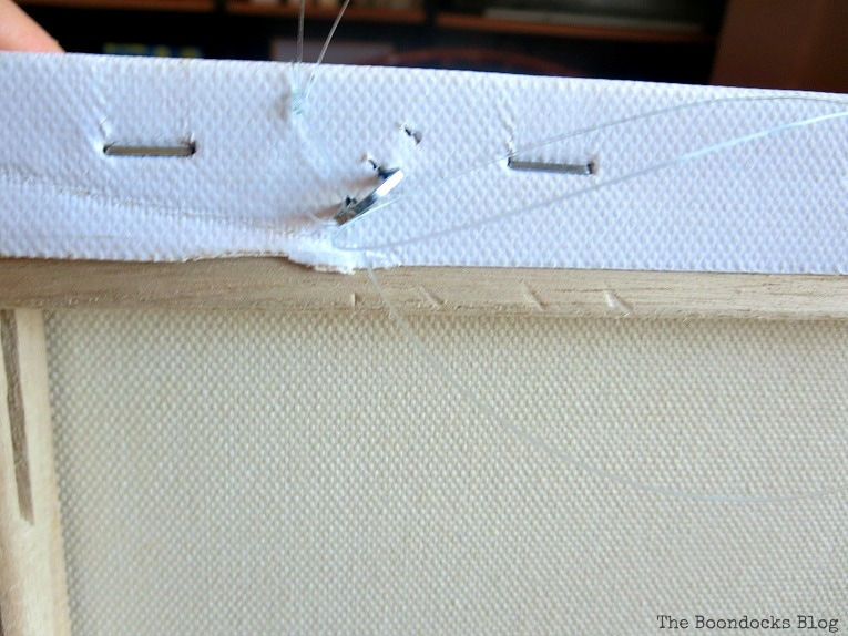 staple which juts out of back of canvas, How to Make Simple Canvas Wall Art with Keys, www.theboondocksblog.com