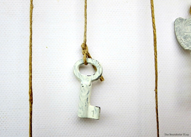 small key tied with thin twine, How to Make Simple Canvas Wall Art with Keys, www.theboondocksblog.com