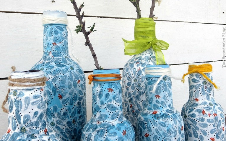 ribbons, yarn and cords added as embellishment to finished decoupaged bottles.