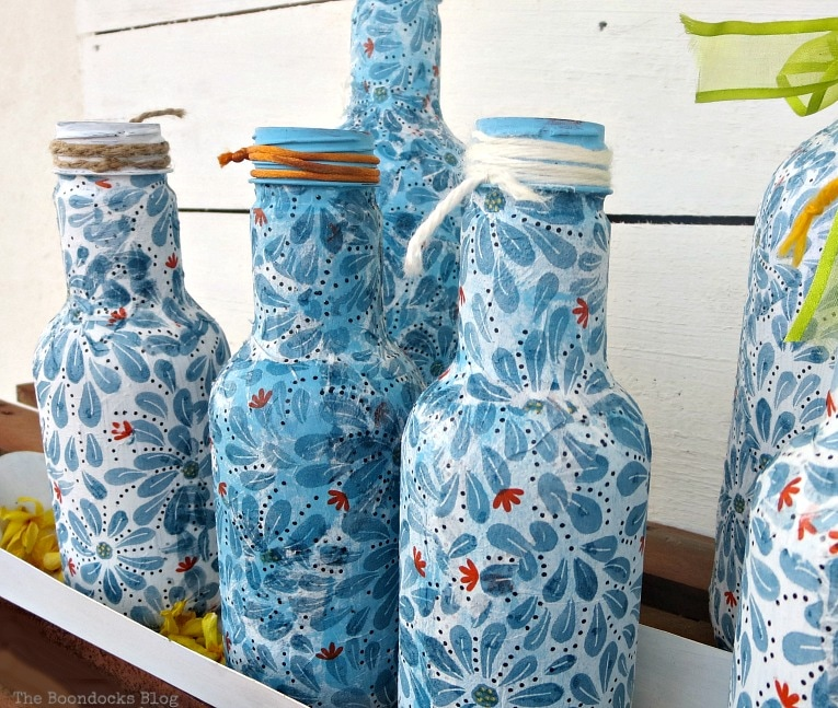 Finished Decoupaged bottles set in achicken feeder.
