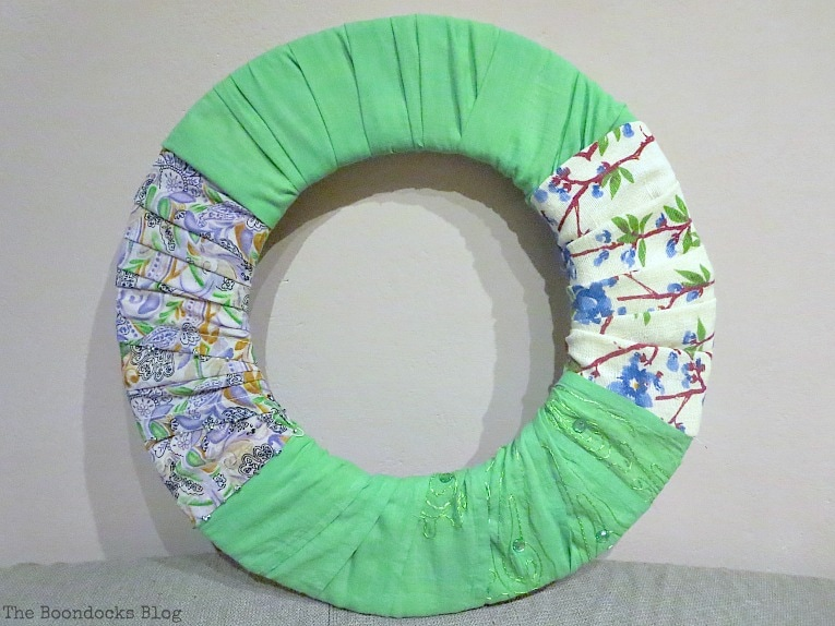 adding green fabric to the wreath, How to Make a Green Wreath for Spring www.theboondocksblog.com