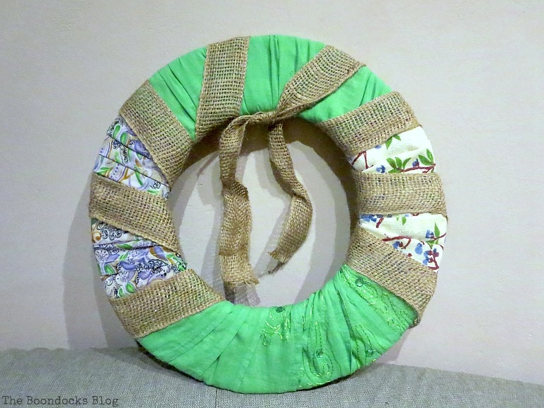 wrapping donut shaped cardboard with burlap ribbon, How to Make a Green Wreath for Spring www.theboondocksblog.com