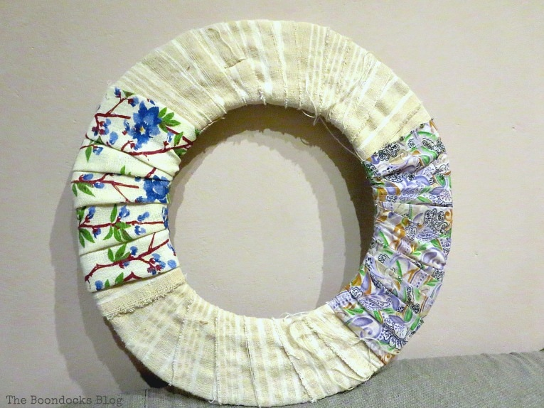 two more fabrics added to the donut shaped cardboard, How to Make a Green Wreath for Spring www.theboondocksblog.com