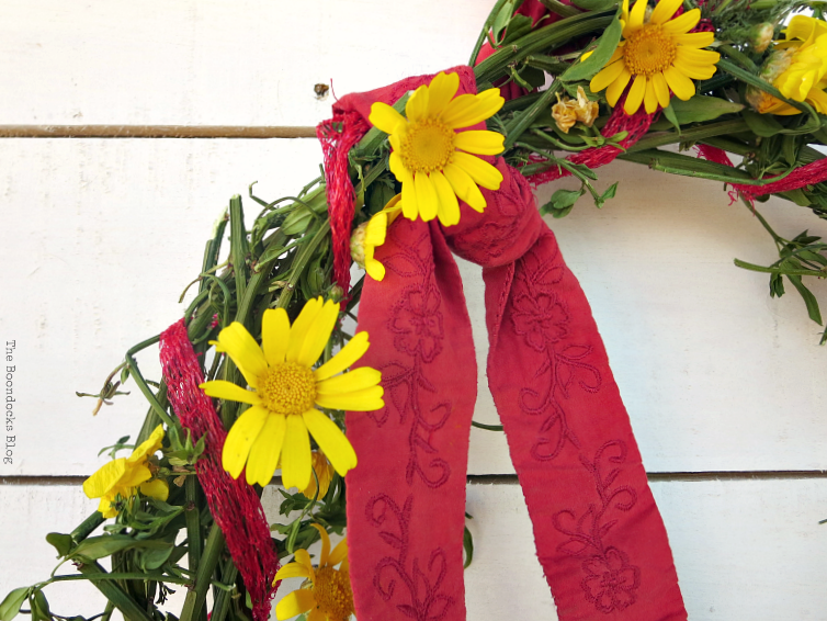 adding a red ribbon for the final touch. How To make May Day Wreaths with Recycled Materials www.theboondocksblog.com