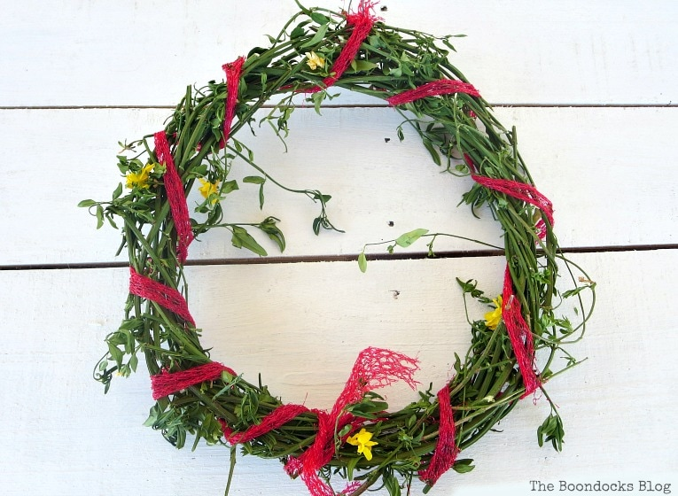wrapping the mess plastic bag around the wreath vines, How To make May Day Wreaths with Recycled Materials www.theboondocksblog.com