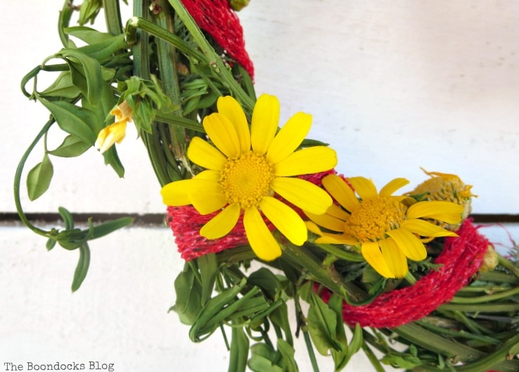 adding yellow daisies to the wreath, How To make May Day Wreaths with Recycled Materials www.theboondocksblog.com
