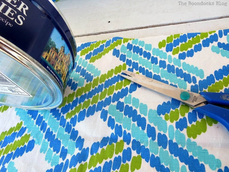 cutting fabric and folding into thirds, How to make pretty cookie tin cans with fabric - IBC www.theboondocksblog.com
