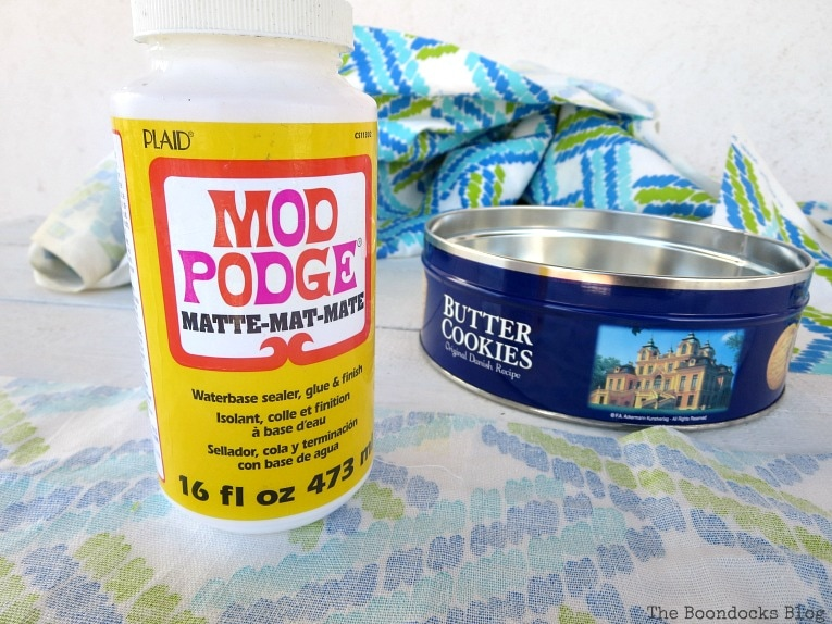 gluing the fabric with mod podge, How to make pretty cookie tin cans with fabric - IBC www.theboondocksblog.com