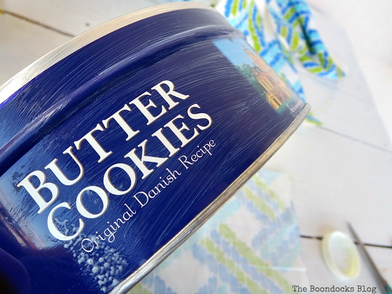 applying mod podge to exterior, How to make pretty cookie tin cans with fabric - IBC www.theboondocksblog.com