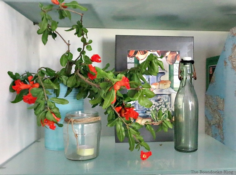 Pomegranate branches added for color to the shelf, Pretty and Practical Bookcases the Easy Way www.theboondocksblog.com