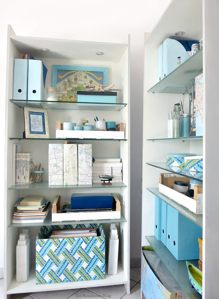 Two bookcases styled with blue colors, maps and pomegranate branches, #bookcasestyling #coastaldecor #summervignettes #upcycledmagazinefiles #upcycledcartons #mapboxes #decoupage #chalkytypepaint #organizing #storagesolutions Upcyled with paint, fabric and decoupage. Pretty and Practical Bookcases the Easy Way www.theboondocksblog.com